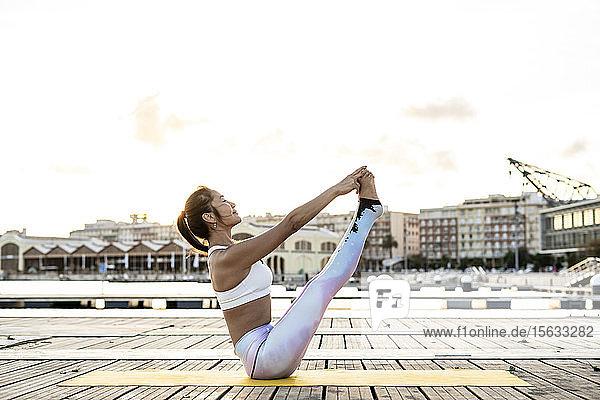 Asiatische Frau  die bei Sonnenuntergang auf einem Pier im Hafen Yoga praktiziert  Bootspose Asiatische Frau, die bei Sonnenuntergang auf einem Pier im Hafen Yoga praktiziert, Bootspose