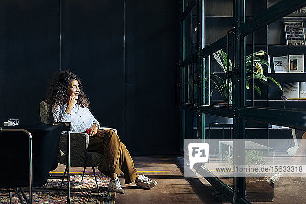 Casual young businesswoman looking out of window in loft office