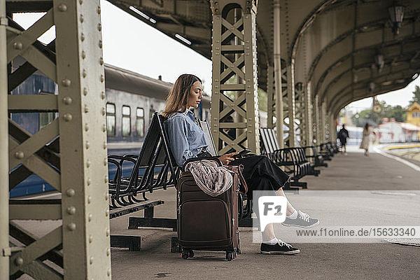 Junge weibliche Reisende wartet am Bahnhof und benutzt E-Book