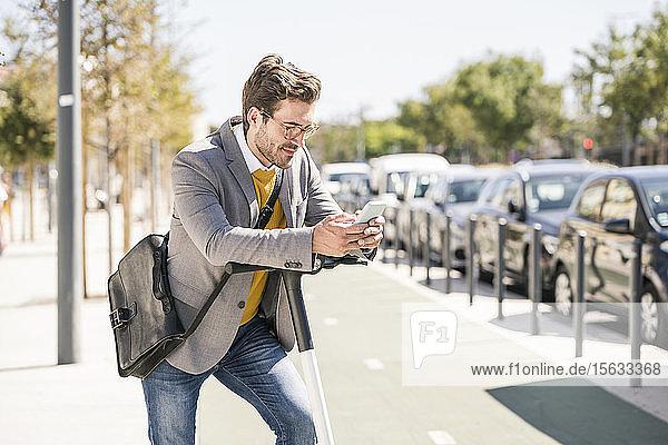Junger Geschäftsmann mit E-Scooter  der sein Handy in der Stadt benutzt
