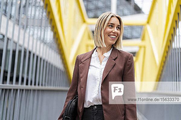 Glückliche junge Geschäftsfrau auf einer Brücke in der Stadt