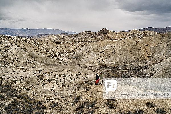 Junges Paar in Wüstenlandschaft unter bewölktem Himmel  Almeria  Andalusien  Spanien