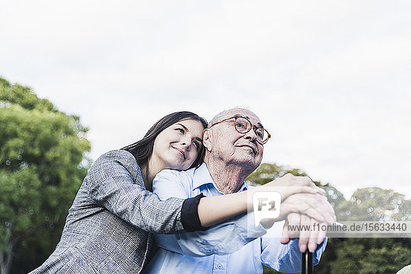 Portrait of young woman hugging her grandfather in a park