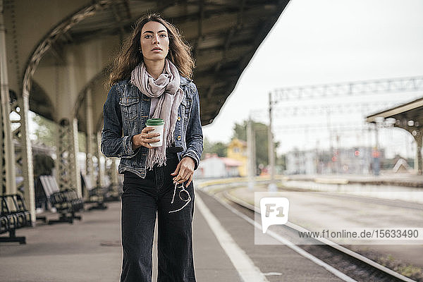 Young female traveller with coffee to go on train station