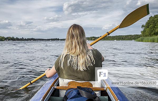 Frau paddelt auf einem See