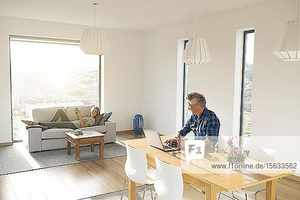 Gelegenheits-Geschäftsmann arbeitet an seinem Laptop im Home-Office und schaut die auf dem Sofa liegende Frau an