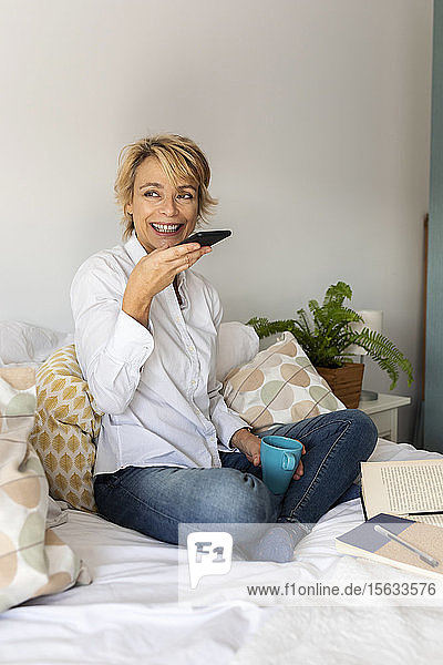 Mature woman sitting on bed at home using smartphone