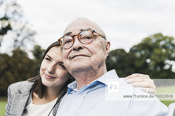 Portrait of self-confident senior man with his granddaughter in a park