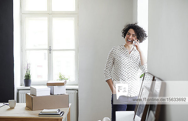 Laughing young woman on the phone in home office