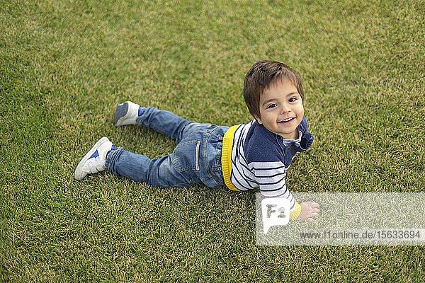 Portrait of smiling little boy lying on lawn