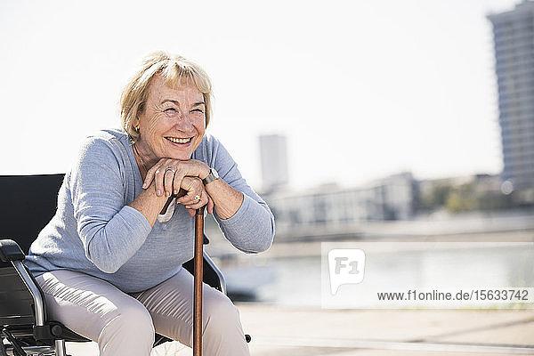 Ältere Frau im Rollstuhl sitzend  mit Gehstock