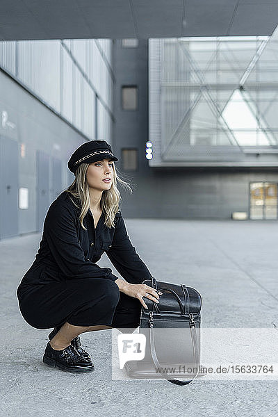 Junge blonde Geschäftsfrau mit Matrosenmütze  die in ihrer Tasche sucht