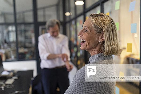 Glückliche Geschäftsfrau mit Kollegin und Haftnotizen an Glasscheibe im Büro
