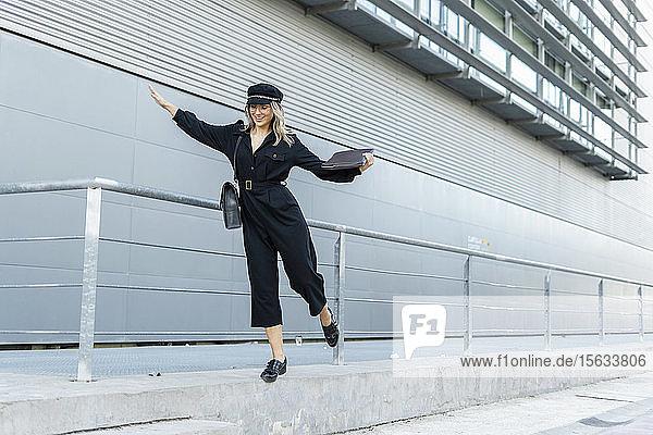Junge blonde Geschäftsfrau mit schwarzer Matrosenmütze und Laptoptasche in der Hand