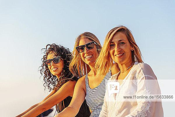 Freunde lachen während der Bootsfahrt im Abendlicht und schauen in die Kamera