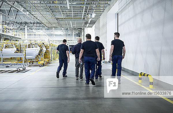 Kollegen machen eine Pause und spazieren in einer modernen Autofabrik