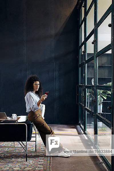 Young businesswoman using smartphone in loft office