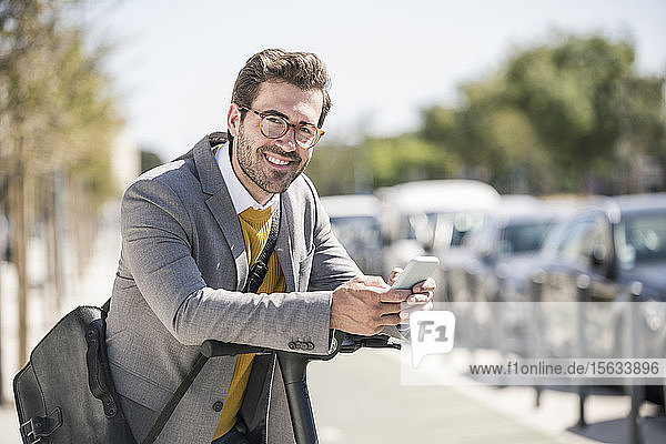Porträt eines lächelnden jungen Geschäftsmannes mit Handy und E-Scooter in der Stadt