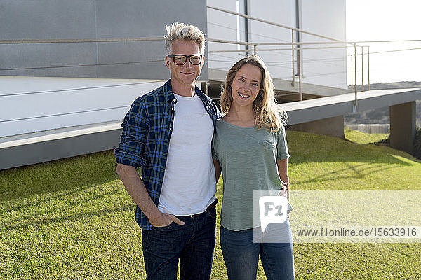 Portrait of smiling couple standing in front of their modern home