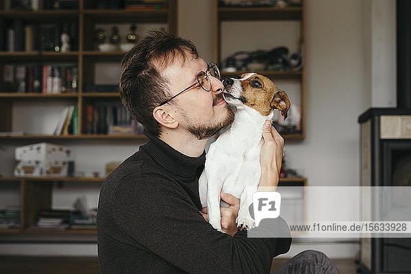 Junger Mann mit Jack Russel Terrier  leckend