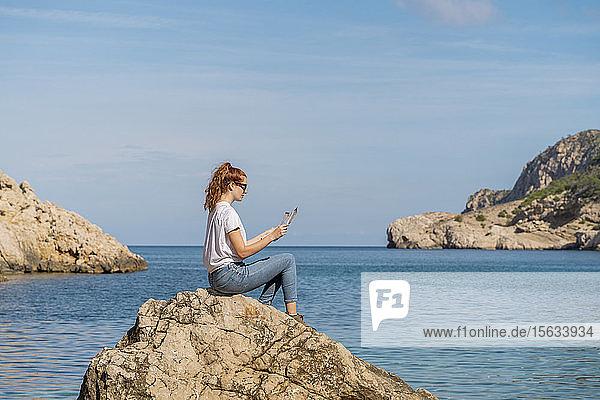 Rothaarige Frau sitzt auf einem Felsen und liest eine Zeitschrift