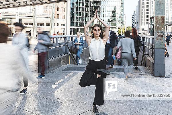 Junge Geschäftsfrau praktiziert Yoga in der Stadt zur Hauptverkehrszeit  Berlin  Deutschland