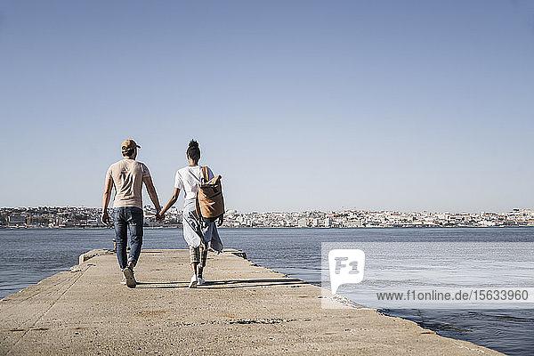 Junges Paar beim Spaziergang am Pier am Wasser  Lissabon  Portugal