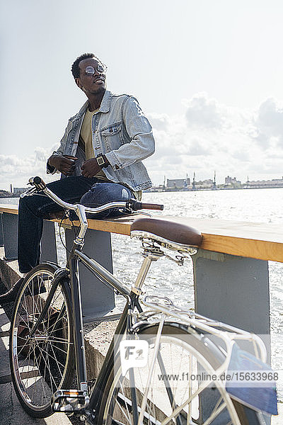 Young amn with bicycle sitting on railing by the sea