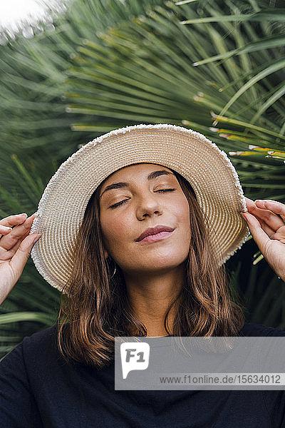 Bildnis einer jungen Frau mit geschlossenen Augen und Sommerhut