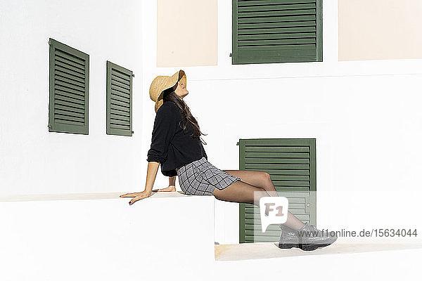 Junge brünette Frau sitzt auf weißer Wand und genießt das Sonnenlicht