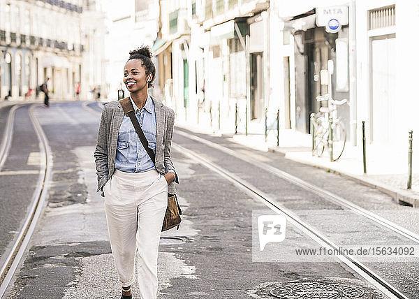 Lächelnde junge Frau mit drahtlosen Kopfhörern in der Stadt unterwegs  Lissabon  Portugal