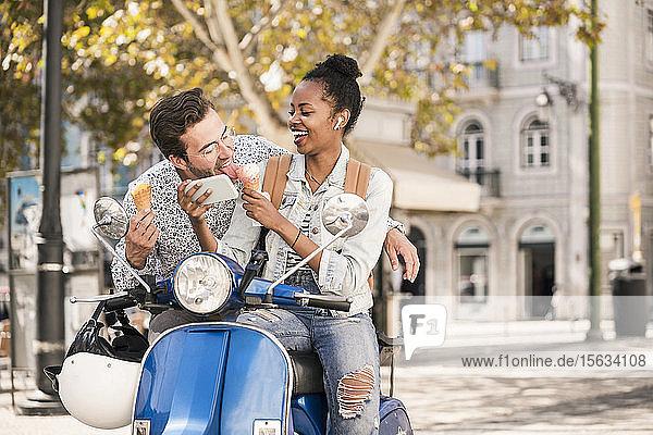 Glückliches junges Paar mit Motorroller  Eiscreme und Mobiltelefon in der Stadt  Lissabon  Portugal
