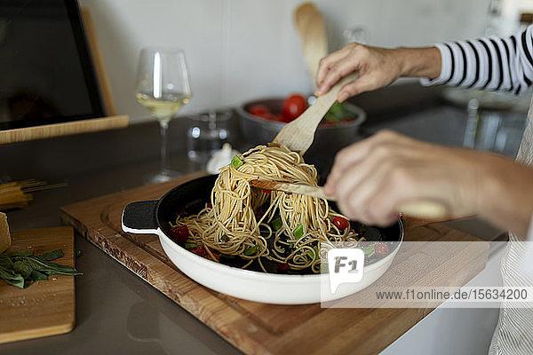 Nahaufnahme einer Frau  die zu Hause in der Küche ein Nudelgericht kocht