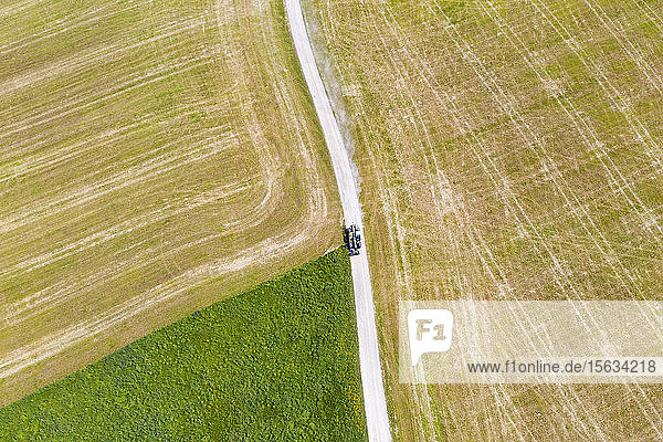 Luftaufnahme eines Traktors auf einem Feldweg inmitten eines landwirtschaftlichen Feldes  Münsing  Deutschland