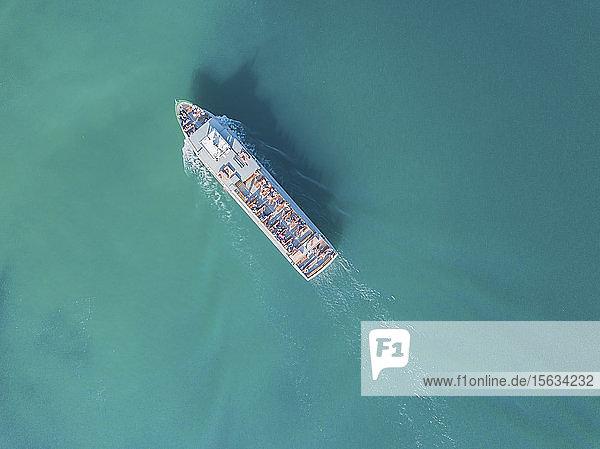 Deutschland  Bayern  Luftaufnahme eines Ausflugsbootes  das über das türkisfarbene Wasser des Chiemsees fährt