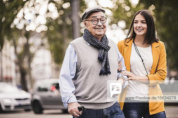 Porträt eines älteren Mannes  der zusammen mit seiner erwachsenen Enkelin spazieren geht