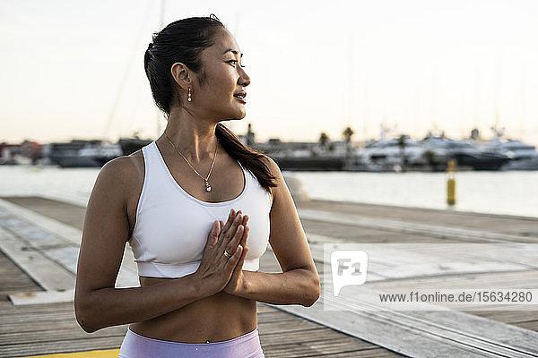 Asiatin  die im Abendlicht auf einem Pier im Hafen Yoga praktiziert  Gebetsposition