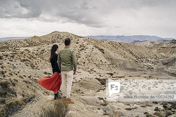 Junges Pärchen in Wüstenlandschaft unter bewölktem Himmel  Almeria  Andalusien  Spanien