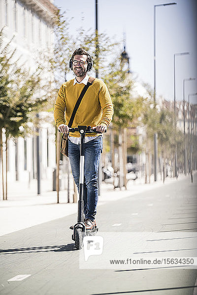 Junger Mann fährt E-Scooter in der Stadt
