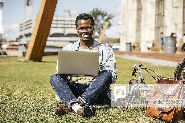 Junger Mann sitzt auf Rasen und benutzt Laptop