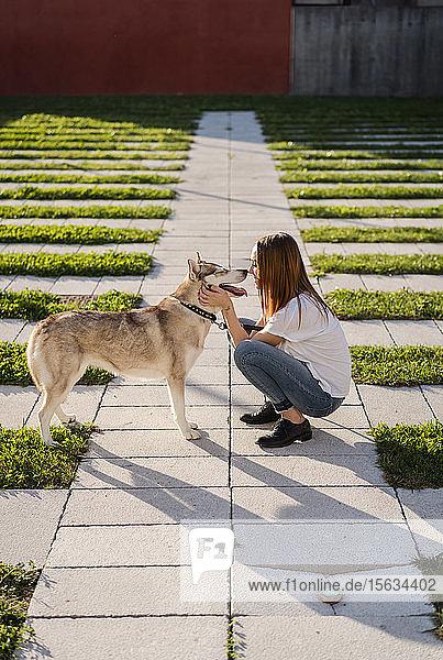Junge Frau kuschelt mit ihrem Hund im Freien