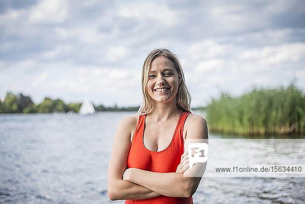 Porträt einer lächelnden Frau  die an einem See steht