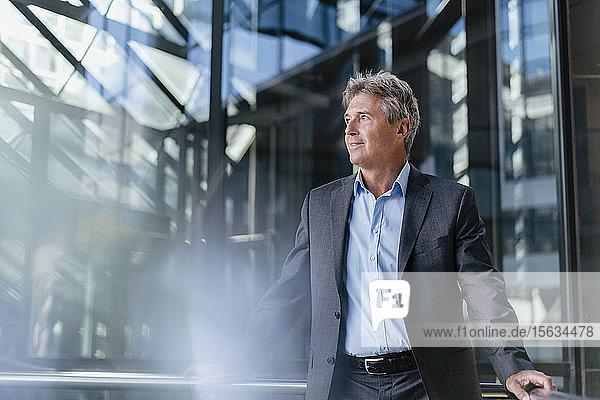 Ein reifer Geschäftsmann steht vor einem Bürogebäude