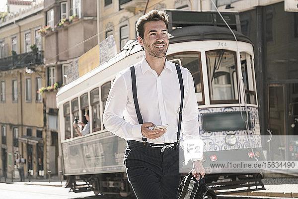 Lächelnder junger Geschäftsmann in der Altstadt unterwegs  Lissabon  Portugal