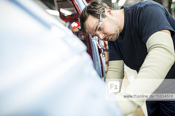Mann arbeitet in moderner Autofabrik