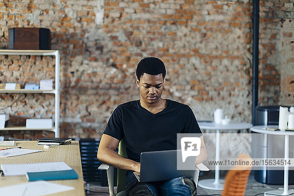 Young man sitting on chair using laptop