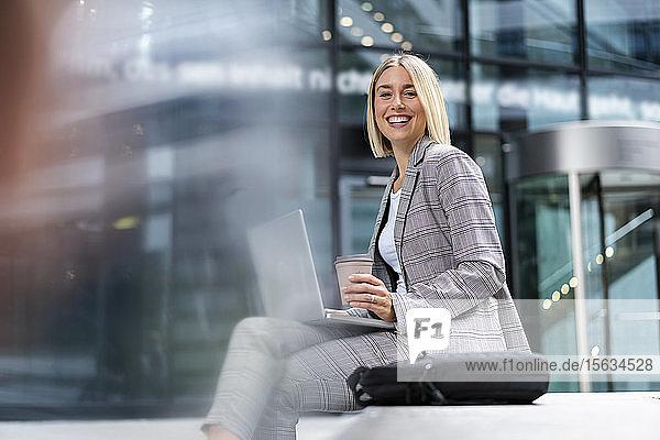 Porträt einer glücklichen jungen Geschäftsfrau mit Laptop in der Stadt