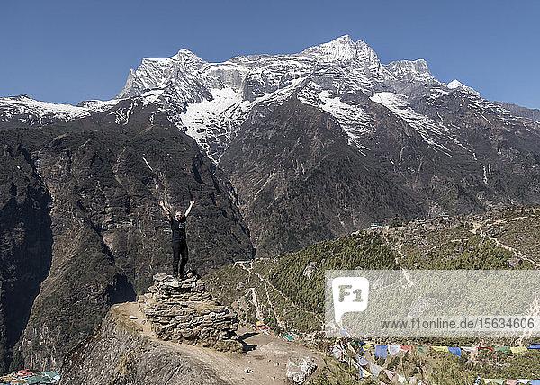 Glückliche Frau hebt die Arme in der Nähe von Namche Bazaar  Himalaya  Solo Khumbu  Nepal