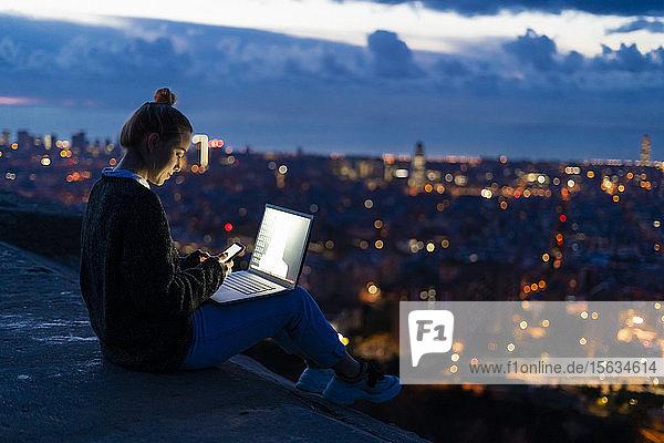 Junge Frau benutzt Handy und Laptop im Morgengrauen über der Stadt  Barcelona  Spanien