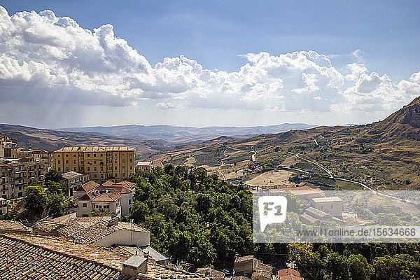 High angle view of houses on mountain against cloudy sky during sunny day  Sicily  Italy
